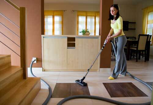 Central Vacuum System- Woman using a Central Vacuum on Floor